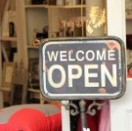 Shop sign in the window that says 'Welcome - Open'